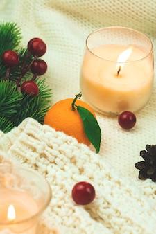 Mandarijn of mandarijn gezellige stillevencompositie in de winter, gebreide trui en kaarsen voor 's avonds. hoge kwaliteit foto