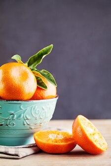 Mandarijn of mandarijnvruchten in blauwe kom op schoolbordachtergrond