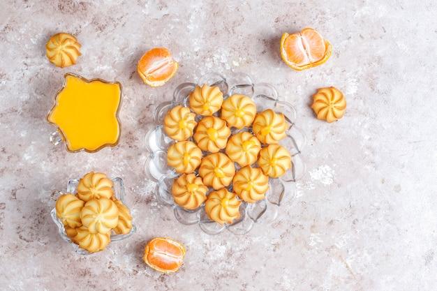 Mandarijn-roomwrongel en koekjes met verse mandarijnen.