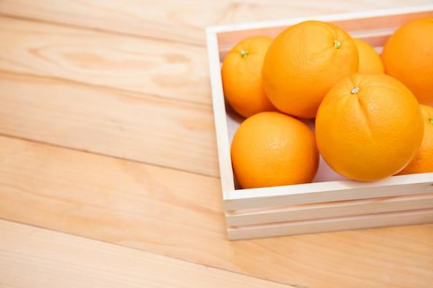 Mandarijn sinaasappelen geplaatst in een houten kist op de tafel. fruit is rijk aan vitamine c en helpt gezonde ogen te behouden en helpt staar voorkomen.