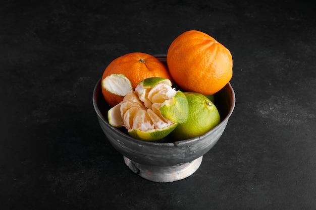 Mandarijn sinaasappelen in een metalen beker op tafel.