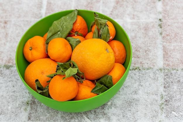 Mandarijnen en sinaasappelen in groene kom op sneeuw staat op straat groene bladeren verwelkt door wintervorst