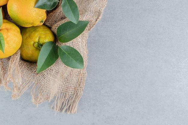 Mandarijnen gebundeld op een stuk stof op marmer.