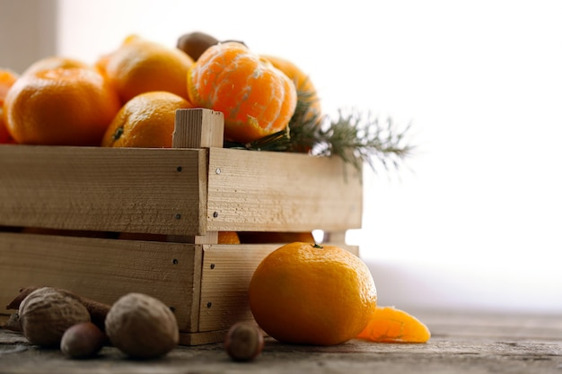 Mandarijnen in houten kist, op oude houten tafel, close-up