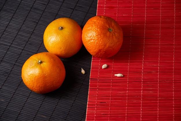 Mandarijnen, mandarijnen, clementines, citrusvruchten op stijl zwarte en rode achtergrond