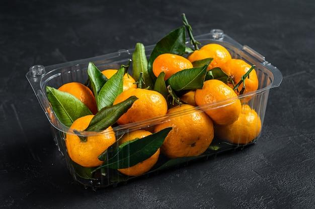 Mandarijnen, mandarijnen in een plastic container, doos. zwarte achtergrond. bovenaanzicht