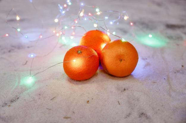 Mandarijnen met glanzende slinger. mandarijnen en slingers lichten. kerstmis of nieuwjaar tafel. verse rijpe mandarijnen. kerstmisstilleven