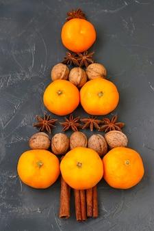 Mandarijnen, noten en anijs in de vorm van een kerstboom op donkere achtergrond