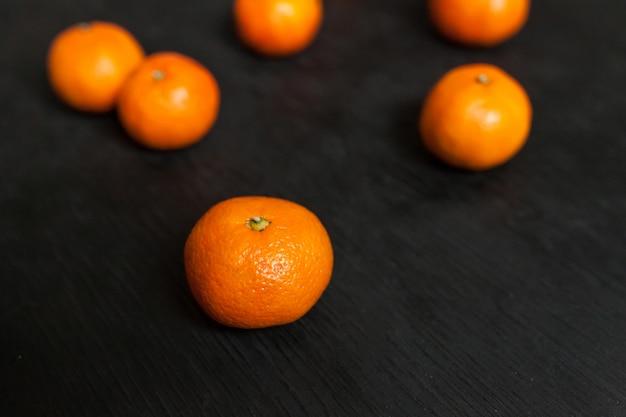 Mandarijnen op een zwarte achtergrond. veel vers fruit - mandarijnen.