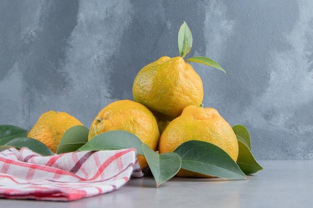 Mandarijnen opgestapeld op een handdoek op marmer.