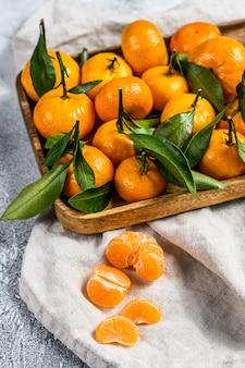 Mandarijnen (sinaasappelen, mandarijnen, clementines, citrusvruchten) met bladeren in houten kom. grijze achtergrond. bovenaanzicht