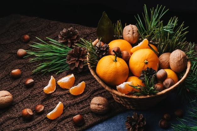 Mandarijnen, walnoten en hazelnoten versierd met dennenappels