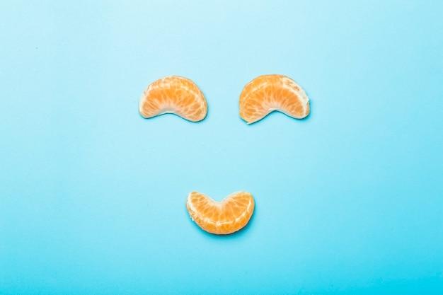 Mandarijnplakken op een lege gekleurde minimale achtergrond. grappig gezicht gemaakt van mandarijnplakken. creativiteit en idee concept.