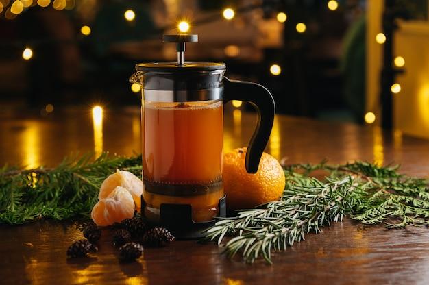 Mandarijnthee in franse pers op de tafel in restaurant. warme drank in de winter en de herfst.