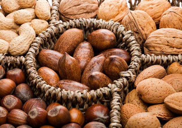 Mandbereik in verschillende soorten noten in schelpen, pecannoten, amandelen, hazelnoten, pinda's en walnoten op witte achtergrond