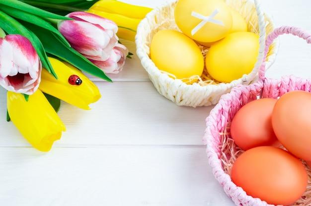 Manden met kleurrijke paaseieren en boeket van tulpen op een witte houten achtergrond.