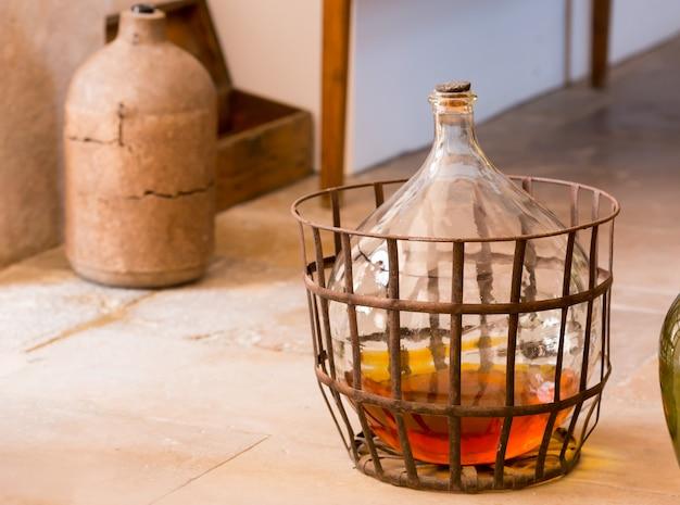 Mandfles met wat drank staat op de vloer in de keuken