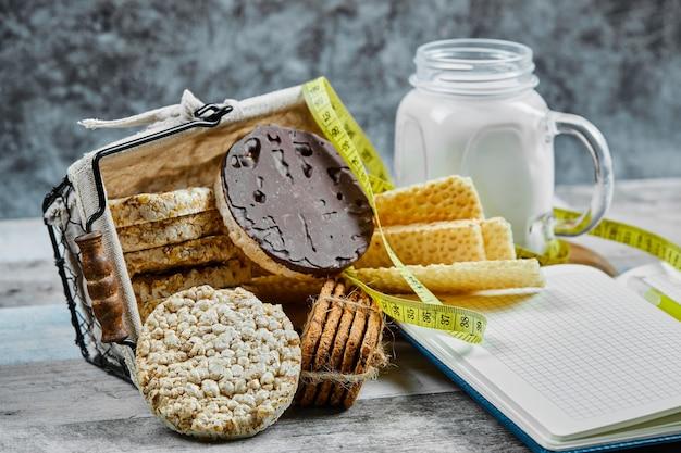 Mandje met koekjes en een potje melk op een houten tafel met een notebook.