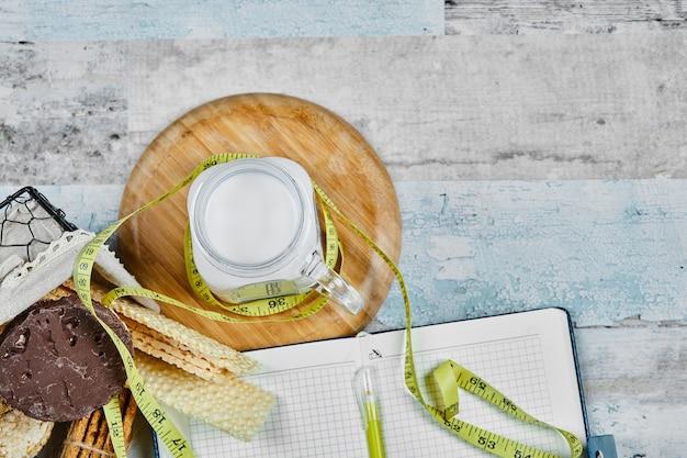 Mandje met koekjes en een potje melk op een marmeren tafel met een notitieboekje.