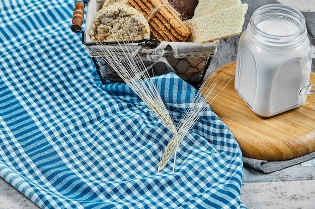 Mandje met koekjes en een potje melk op een marmeren tafel met een tafelkleed.
