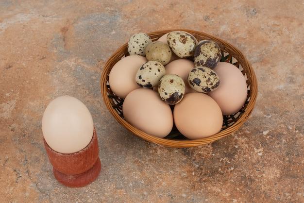 Mandje met witte eieren op marmeren tafel.