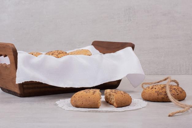 Mandje van koekjes met sesamzaadjes op witte ondergrond.