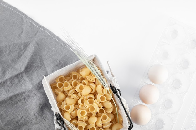 Mandje van rauwe pasta en eieren in container op wit oppervlak.