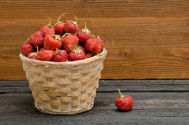 Mandje van rijpe aardbeien op zwarte houten tafel