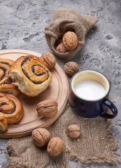 Mandje van zelfgemaakte broodjes met jam, geserveerd op oude houten tafel met walnoten en kopje melk