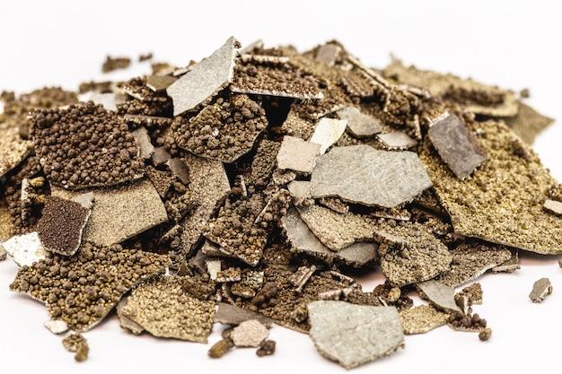 Mangaanmonsters, vlokken puur mangaanmetaal gebruikt in de industrie, geïsoleerde witte achtergrond.