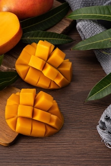 Mango. close up van vers rijp mango fruit met bladeren over donkere houten tafel achtergrond met groene bladeren.