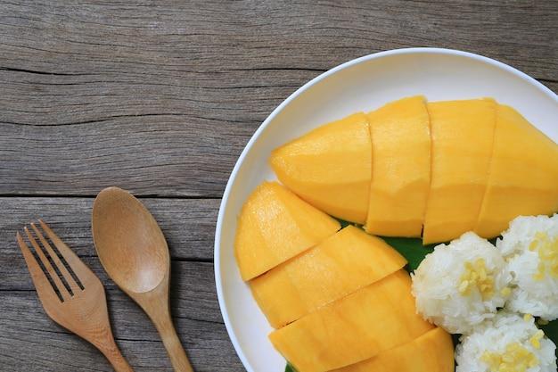 Mango en kleverige rijst in de witte schotel op houten vloer