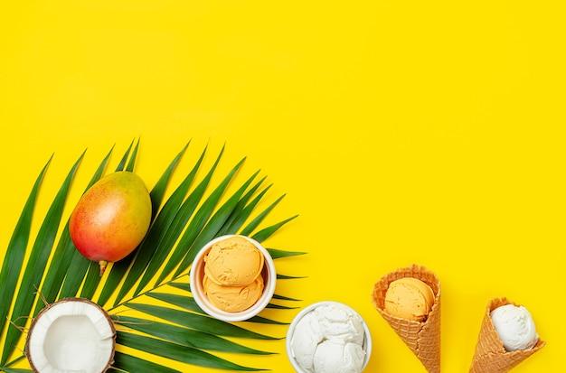 Mango en kokosroomijs met palmblad op gele achtergrond. plat leggen, ruimte kopiëren.