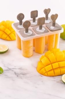 Mango ijslolly, fruitijs in de plastic vormdoos op heldere marmeren tafel. zomer verfrissing concept product designelementen, objecten, close-up.