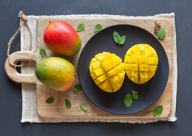 Mango in tweeën gesneden en in blokjes gesneden op een houten bord, twee hele mango. bovenaanzicht