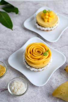 Mango mousse taart met kleefrijst en verse mango. ingesteld op witte café tafel.