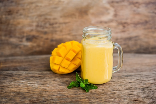 Mango smoothie in een glazen mason pot en mango op de oude houten achtergrond. mango shake.