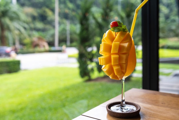 Mango smoothie in glas op houten tafel
