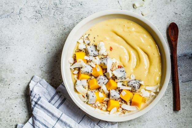 Mango smoothie kom met granola en dragon fruit in witte kom, bovenaanzicht. gezond ontbijt concept.