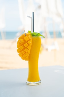 Mango smoothies glas met zee strand achtergrond