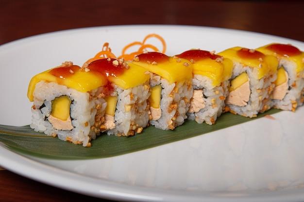Mango sushi, foie gras, pinda en mangosaus geserveerd op een witte plaat. japanse keuken