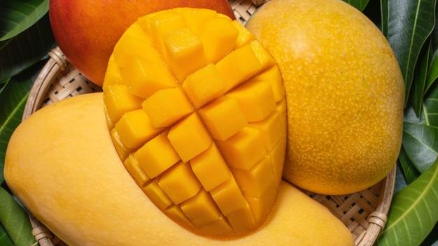 Mango, tropisch fruit, in een bamboe houten zeefmand op groene bladachtergrond, bovenaanzicht, volledig frame, mooi, rijp oogstontwerpconcept.