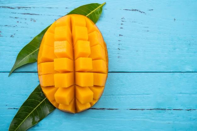 Mango - vers gehakt tropisch mangofruit geïsoleerd op heldere levendige lichtblauwe houten tafel achtergrond, bovenaanzicht, plat lay-out, overhead schot.