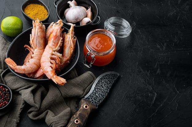 Mangochutney grote rauwe schaal op rauwe gamba's ingrediënten in kom, op zwarte achtergrond, met copyspace en ruimte voor tekst