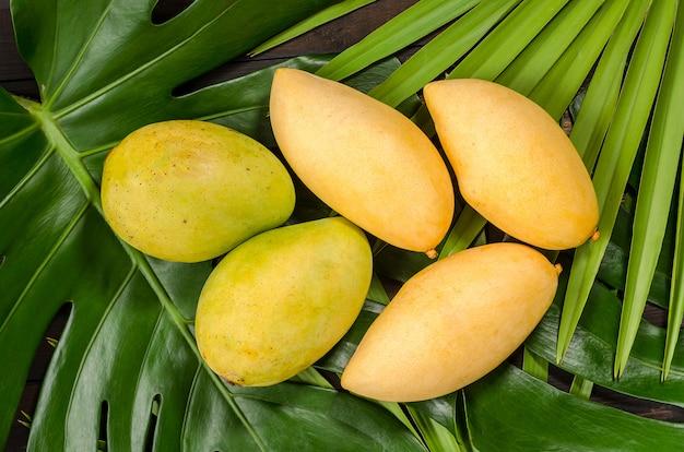 Mangofruit op groene bladeren, op houten achtergrond.