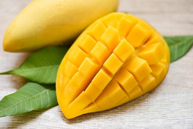 Mangoplak en mangobladeren van het fruitconcept van de boom tropisch zomer - zoete rijpe half gesneden mango's
