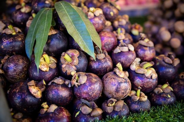 Mangostan en groene bladeren bij marktwinkel thailand