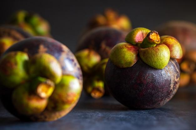 Mangostanfruit op zwart cementvloer en ochtendlicht. is een seizoensfruit in thailand. close-up en copyspace.
