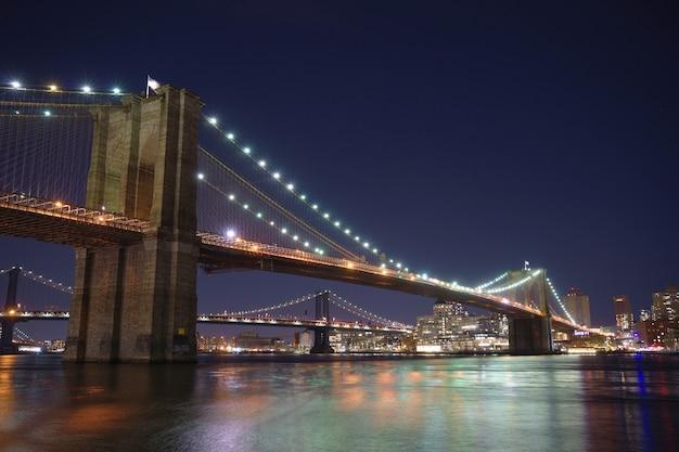 Manhattan bridge en brooklyn skyline met mooie wazig weerspiegeling in de rivier 's nachts