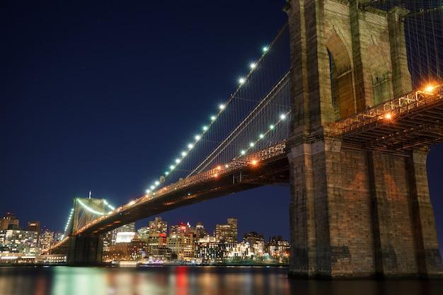 Manhattan bridge en brooklyn skyline met mooie wazige reflectie in de rivier 's nachts